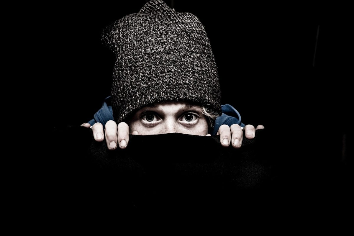 Boy in a hat looking scared and shy
